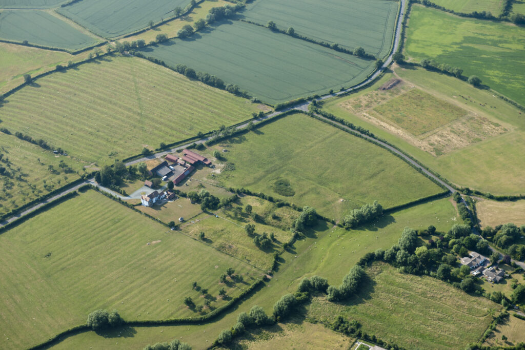This large scale, isolated farmstead, located to the west of the village of Naunton Beauchamp, is on the site of a small medieval manor, believed to have been created during the land hunger of the 13th and 14th centuries. The remains of a late 15th or early 16th century moated site are recorded to the east (the right) of the farmstead. The late 16th century timber-framed Court House is detached from the agricultural buildings, which developed piecemeal around a central and additional smaller yard to the left. The farmstead retains its loose courtyard plan and over 50% of its traditional buildings survive despite the incorporation of 20th century sheds on, and to the north of, the central yard. Photo © English Heritage NMR 27792/019.